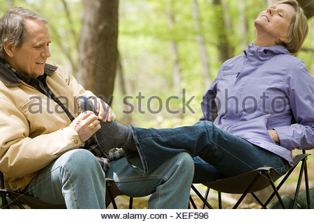 Man massaging his wifes feet in forest - Stock Photo