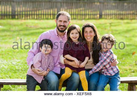 Family sitting on bench together looking at camera smiling - Stock Photo
