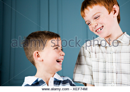 Older and younger boy laughing together - Stock Photo