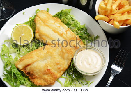 A plate of fried Fish and Chips served on lettuce - Stock Photo
