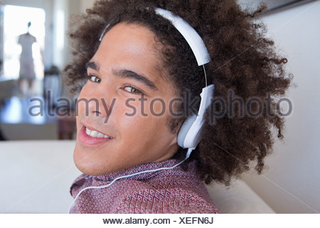 Close up portrait of confident young man wearing headphones - Stock Photo