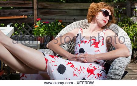 Woman sunbathing in patio chair - Stock Photo