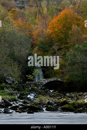 Waterfall surrounded by Autumn leaves with old stone arched bridge and river in foreground, Glen Lyon, Perth and - Stock Photo