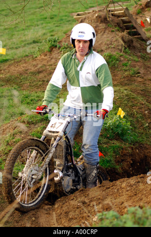 motorcycle trials rider negotiating tricky section of course on specialist built machine / motorbike - Stock Photo