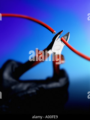 Gloved hand cutting red wire with wire cutters - Stock Photo