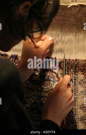 Young girl weaving a carpet in Bokhara Uzbekistan - Stock Photo
