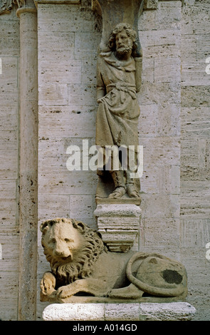 Carving of Lion Saint decorates the front of a Church in the town of SAN QUIRICO D ORCIA TUSCANY ITALY - Stock Photo
