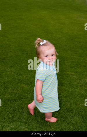 Fourteen Month Old Girl on Grass in Park - Stock Photo