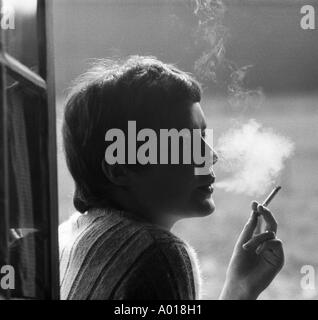 health, young girl, young woman smoking a cigarette, smoke, back light, b&w, black and white, black & white photography - Stock Photo