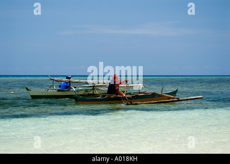 Fishing outrigger canoes off the beach at Gangga Island dive resort near Manado North Sulawesi Indonesia - Stock Photo