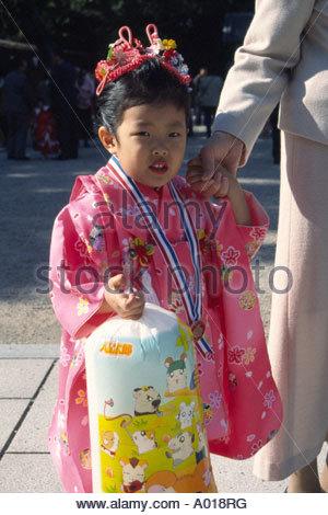 Japan, Nishinomiya. Girl, 3 years old, wearing pink, red kimono, walking by holding mother's hand, and bag of goodies - Stock Photo
