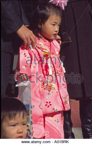 Japan, Nishinomiya. Girl, 3 years old, in pink kimono, posing for picture with father's hands holding her shoulders. - Stock Photo