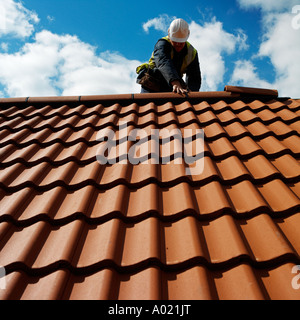Roof tiler lays tiles on a new house england No release required, features of face totally hidden man is unrecognizable - Stock Photo