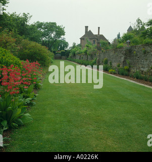 Large rectangular lawn in walled country garden with herbaceous border - Stock Photo