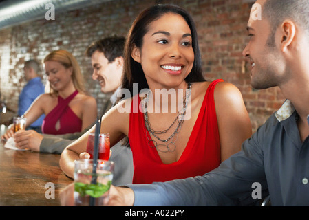 Couple holding cocktails, sitting at bar - Stock Photo