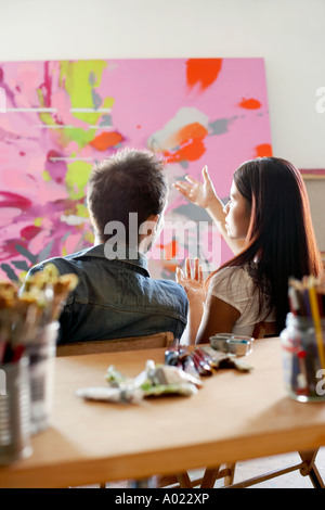 Couple discussing  painting in artist's studio, back view - Stock Photo