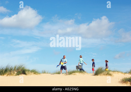 Vacationing Family walking along beach - Stock Photo