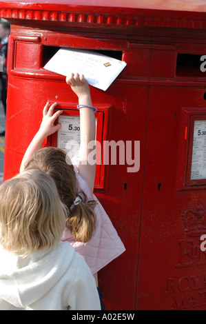 Young girl posting a letter in to a large red British Post Office box - Stock Photo