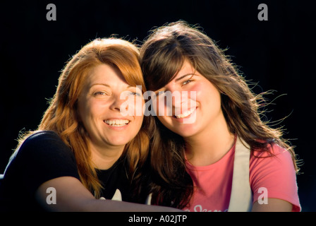 Mother and daughter similing and looking at the camera - Stock Photo