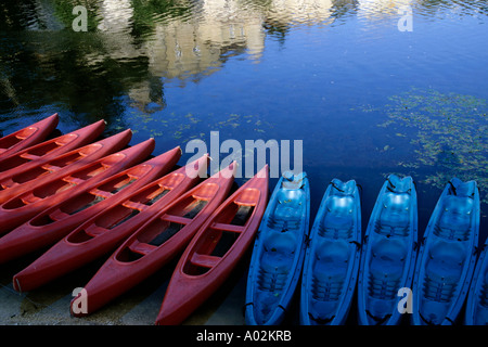 Kayaks lined up along the Lot riverbank at sunset, Puy-L'Eveque, Lot, France. - Stock Photo
