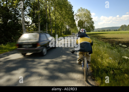 Speeding car passing a young mountain biker on a countryside road - Stock Photo