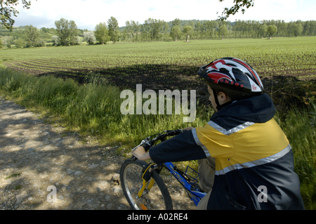 A mountain biker on a dirt road - Stock Photo