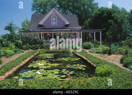 Pastel lavender painted wood house landscaped with brick and a large decorative fish and lily pool with walkway - Stock Photo