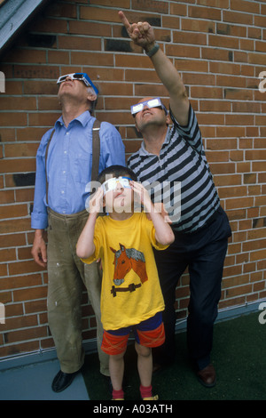 grandfather, father and son watching a penumbral solar eclipse - Stock Photo