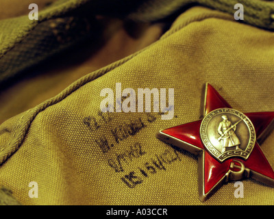 Red Army (Soviet) long service medal in the shape of a red star, laying on top of a canvas rucksack. - Stock Photo