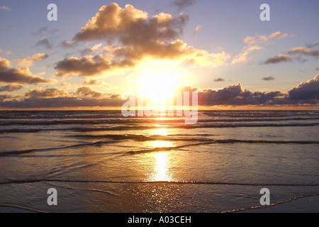 Colorful sunset over the gentle waves of the Pacific Ocean and a silhouetted beach on the coast of Oregon. - Stock Photo
