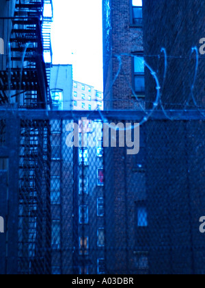 Coils of barbed wire atop a wrought iron fence in front of an alleyway on the upper west side of New York City. - Stock Photo