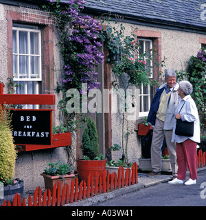 MATURE COUPLE ARRIVING AT BED BREAKFAST LUSS LOCH LOMOND SCOTLAND - Stock Photo