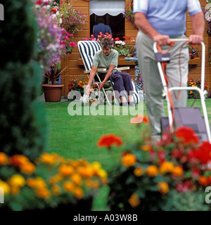 MAN MOWING LAWN WHILE WIFE ATTENDS TO PLANTS.MODEL RELEASE AVAILABLE ON REQUEST. - Stock Photo
