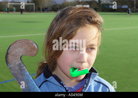 Young girl hockey player tired after hockey match with stick and gumguard - Stock Photo