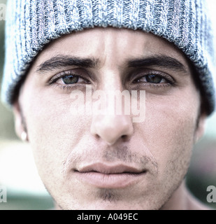 Close up portrait of a young man wearing a grey wool hat - Stock Photo