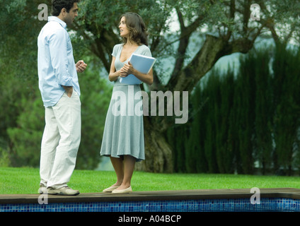 Man and woman talking by side of pool - Stock Photo