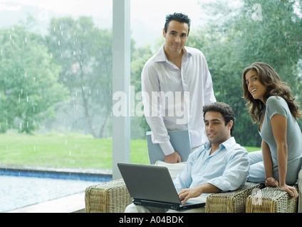 Casually dressed executives working by side of pool - Stock Photo