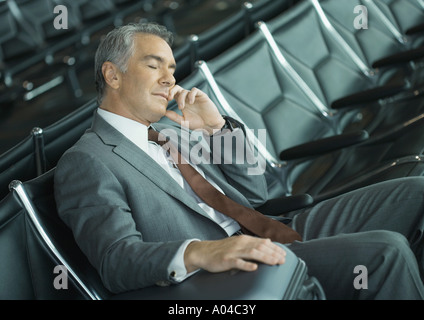 Businessman sleeping in airport lounge - Stock Photo