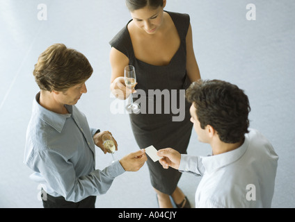 Executives exchanging business card during cocktail party - Stock Photo