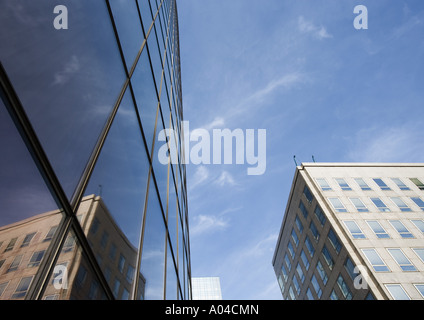 Building reflected on skycraper windows, low angle view - Stock Photo