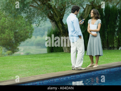 Man and woman standing near edge of pool with documents and cell phone - Stock Photo