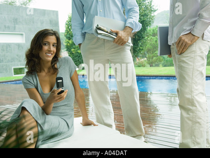 Casually dressed young executives working near edge of pool - Stock Photo