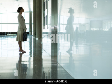 Woman standing in airport concourse - Stock Photo