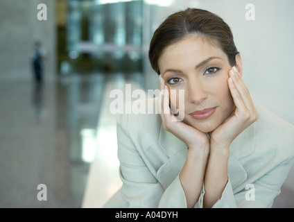 Woman cupping head in hands - Stock Photo