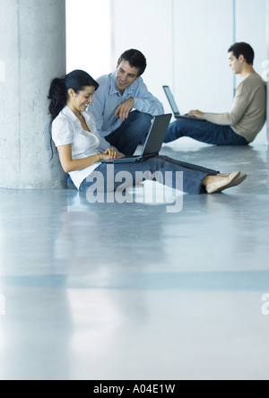 Man and woman on floor, using laptop and talking, second man in background - Stock Photo