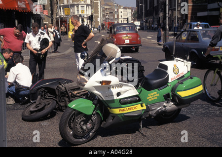 Paramedic from London Ambulance service police bystanders assist motorbike courier rider after involvement in road - Stock Photo