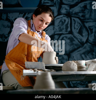 Teenage girl shaping pottery on a pottery wheel in a high school art class. - Stock Photo
