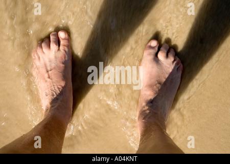 Feet standing,  receding  tide. - Stock Photo