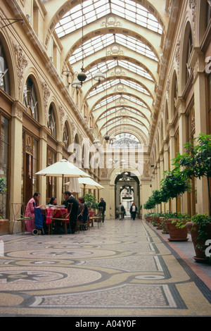 Passageway and glass ceiling of the gallery Vivienne in Paris, France. Galerie Vivienne in the 2nd arrondissement. - Stock Photo