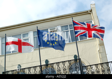 English flag of St George, British Union Flag, and European Union flay flying side by side - Stock Photo